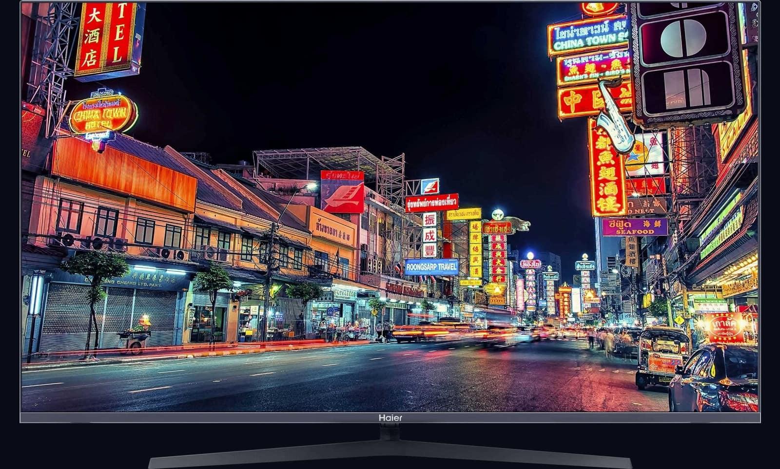 Экран Haier Smart TV с изображением улицы с яркими вывесками
